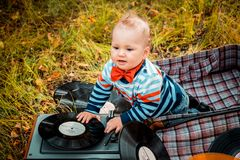 Little one-year-old child sitting in an old retro suitcase in the fall outdoors royalty free stock photos