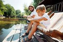 Little open-eyed blond boy and his handsome father are sitting in recliners on the wooden pier and fishing. stock photo