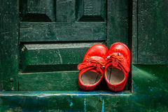 Little orange shoes. Shoes left at a green door Stock Photos