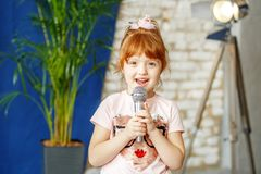 The little ore girl sings to the microphone. The concept is chil royalty free stock photography