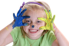 The little painter. Young Child (Girl) smiles after painting session with colorful hands Royalty Free Stock Photography