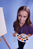 Little painter. And easel and brushes Stock Photography