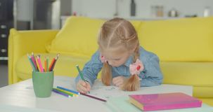 Little painter with felt tp pen drawing artwork. Positive girl with pigtails engrossed in drawing, creating artwork with colored felt-tip pens in domestic room stock footage