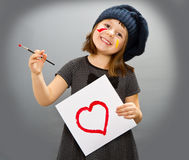 Little painter girl with a drwan heart isolated on grey Royalty Free Stock Images
