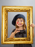 Little painter girl  looking through a vintage picture frame Royalty Free Stock Photography
