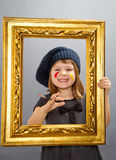 Little painter girl  looking through a vintage picture frame Stock Photos