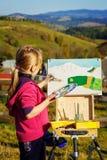 Little painter at work near waterfall Stock Photo