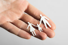 Little paper cutout family on hand Stock Images