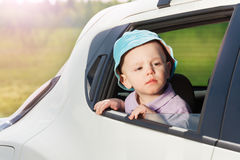 Little passenger peering out the open car window Stock Images