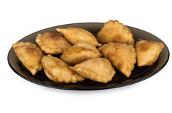 Little pasties on black transparent dish isolated on white Stock Photos