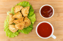 Little pasties on lettuce leaves, bowl with sauce and juice Royalty Free Stock Image