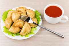 Little pasties with lettuce leaves in glass plate,  tomato sauce Stock Images