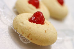 Little pastry with cherry. Little yellow pastry with cherry on top Stock Images