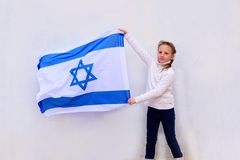 Little patriot jewish girl with the flag of Israel on white background. stock images