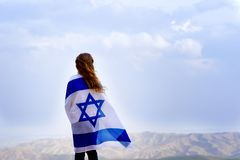 Israeli jewish little girl with Israel flag back view. Little patriot jewish girl standing and enjoying great view on the sky, valley and mountains with the stock photos