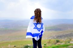 Israeli jewish little girl with Israel flag back view. Little patriot jewish girl standing and enjoying great view on the sky, valley and mountains with the royalty free stock images