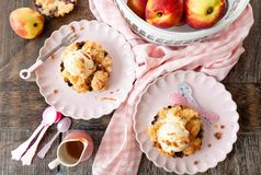 Little peach crumble with ice cream. Peach crumble a la mode, with a scoop of vanilla ice cream royalty free stock image
