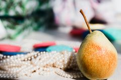 Little pear and strands of pearls stock photo