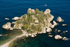 Little peninsula, Isola Bella, people at the beach, small boats around, blue sea in Taormina, Sicily, Italy. Famous little isle in east Sicily sea shore. Sunset stock image