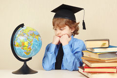 Little pensive boy in academic hat looks at a globe among old books Royalty Free Stock Photos