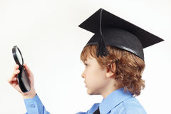 Little pensive boy in academic hat with a magnifying glass on white background Royalty Free Stock Photos