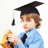 Little pensive boy in academic hat with old abacus on white background Royalty Free Stock Photo