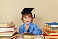 Little pensive boy in academic hat among old books Stock Image