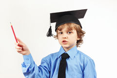 Little pensive boy in academic hat with pencil on white background Stock Image