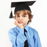 Little pensive boy in academic hat on white background Stock Photos