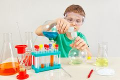 Little pensive boy in safety goggles studies chemical practice in laboratory Stock Images