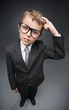 Little pensive businessmen in glasses scratches head Royalty Free Stock Photography