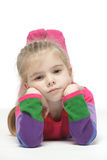 Little pensive girl lying down on the floor Stock Photos