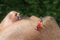 Little People Mowing Hair off a Mans Face. Miniature Life People Mowing Hair off a Mans Face Stock Photography