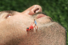 Little People Mowing Hair off a Mans Face. Miniature Life People Mowing Hair off a Mans Face Royalty Free Stock Photo