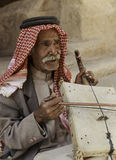 Little Petra, Jordan – June 20, 2017: Old Bedouin man or Arab man in traditional outfit, playing his musical instrument . Little Petra, Jordan – June 20 Stock Image