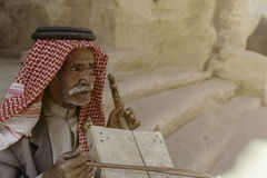 Little Petra, Jordan – June 20, 2017: Old Bedouin man or Arab man in traditional outfit, playing his musical instrument . Royalty Free Stock Photo