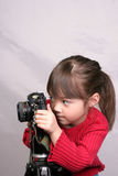 The little photographer. A young girl plays with an older camera Stock Images
