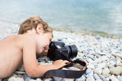 Little photographer on beach taking pictures sea Stock Image