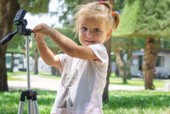 Little Photographer with Professional Tripod, girl playing outdoors Stock Image