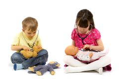 Little Physicians With Stethoscopes. Young boy and girl with stethoscopes, checking the heartbeat of a doll and stuffed animal.  Taken in studio, isolated on Stock Images