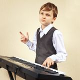Little pianist in suit playing the electronic piano Royalty Free Stock Photo