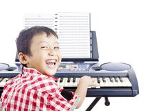 Little piano player. Portrait of little piano player smiling and playing the piano. shot in studio isolated on white Royalty Free Stock Photos