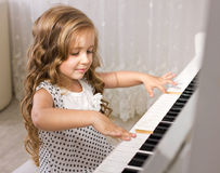 Little piano player. Beautiful little girl playing piano in light room Royalty Free Stock Photography