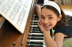 Little Piano Player. Young Hispanic pianist poses with her instrument Stock Photo