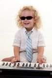 Little piano player. Adorable little three year old boy with curly blond hair wearing white shirt and tie and sunglasses playing a piano keyboard Stock Photography