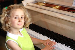 Little piano player. Little  blond girl playing piano Royalty Free Stock Photos
