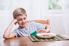 Little picky eater. Sitting at the table royalty free stock photos