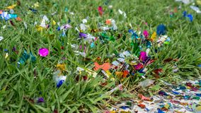 Little pieces of decorative paper on green grass at ancestor graveyard for decoration. Little colorful pieces of decorative paper on green grass at ancestor stock photo