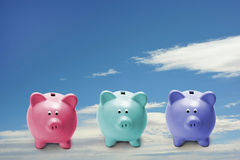 Little piggy bankS. Three little piggy banks flying high in the sky Stock Image
