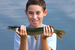 Little Pike. Caucasian smiling boy with a small pike in hands; focus on the fish Stock Images